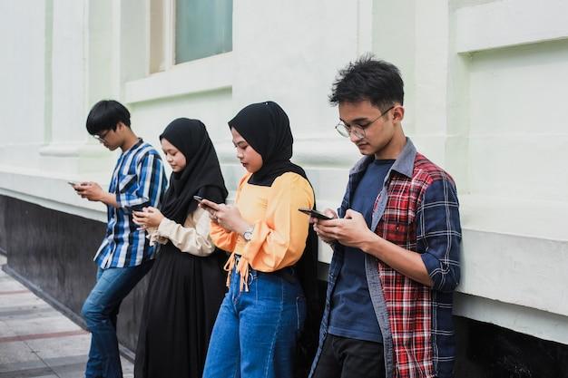 Grupo de amigos que utilizan teléfonos móviles inteligentes