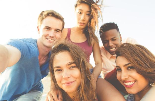 Grupo de amigos de raza mixta caminando en la playa de santa mónica y tomando selfies