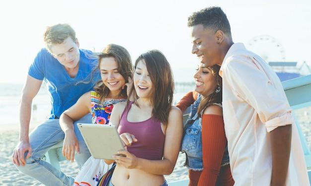 Grupo de amigos de raza mixta disfrutando del tiempo juntos en la playa viendo videos divertidos en las redes sociales