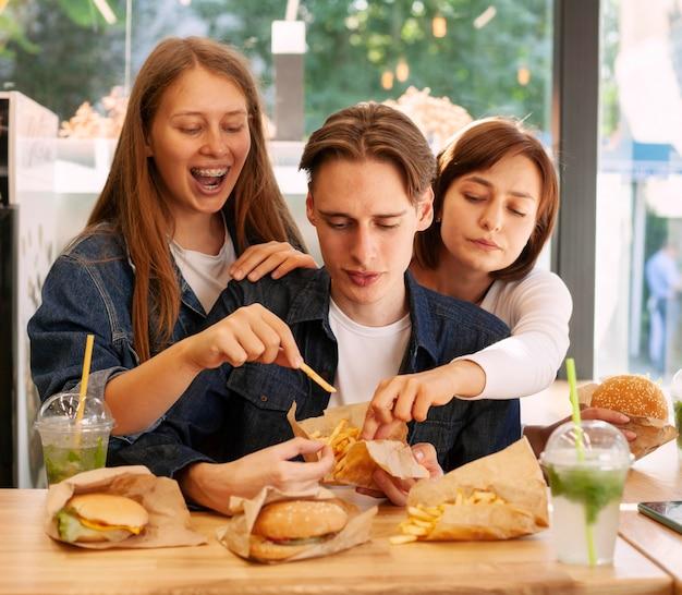 Grupo de amigos en el restaurante de comida rápida comiendo hamburguesas