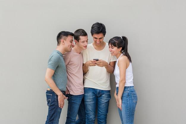 Grupo de amigos revisando un teléfono móvil