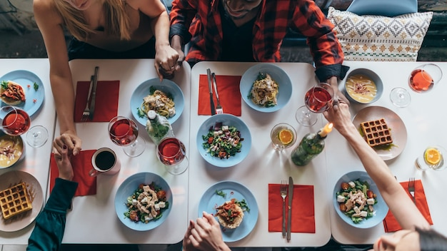 Grupo de amigos rezan antes de comer. vista superior de la reunión familiar en casa para cenar