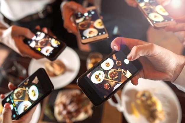 Grupo de amigos saliendo y tomando una foto de comida junto con un teléfono móvil.