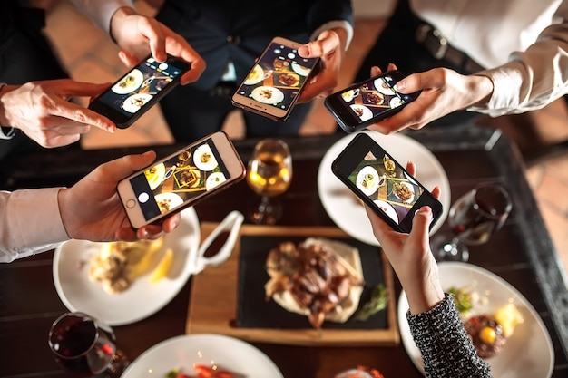 Grupo de amigos saliendo y tomando una foto de comida junto con el teléfono móvil