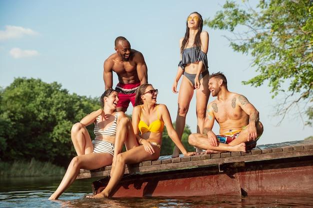 Grupo de amigos salpicando agua y riendo en el muelle en el río