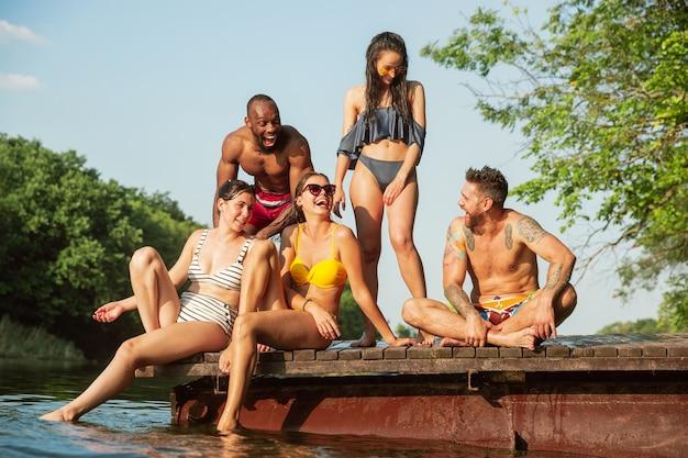 Grupo de amigos salpicando agua y riendo en el muelle sobre el río
