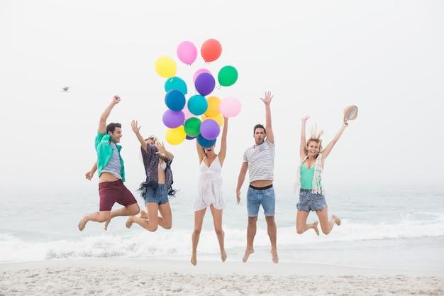 Grupo de amigos saltando en la playa con globos