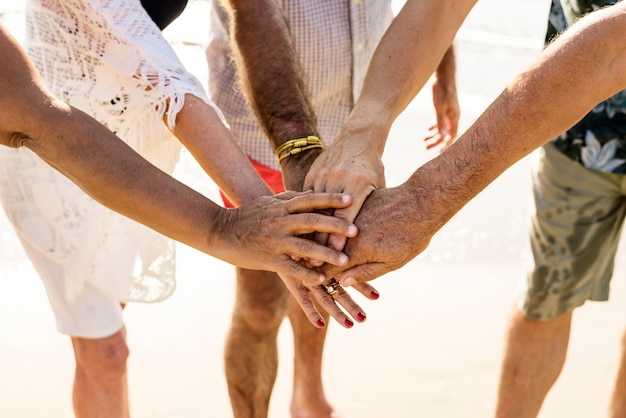 Grupo de amigos senior apilando las manos