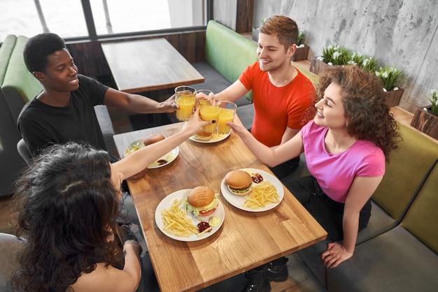 Grupo de amigos sentados en la cafetería a la mesa, tintineo de vasos.