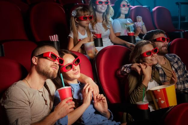 Grupo de amigos sentados en el cine con palomitas y bebidas