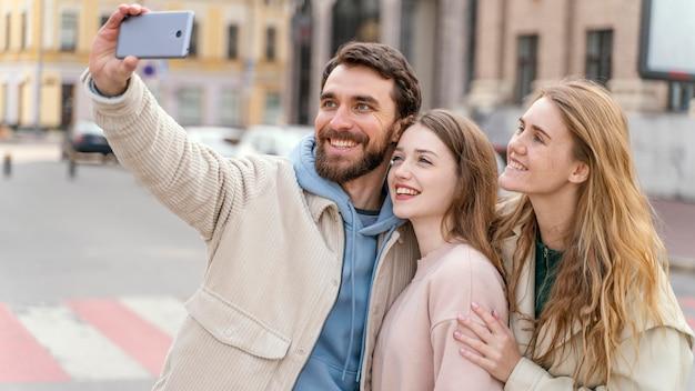 Grupo de amigos sonrientes al aire libre en la ciudad tomando selfie