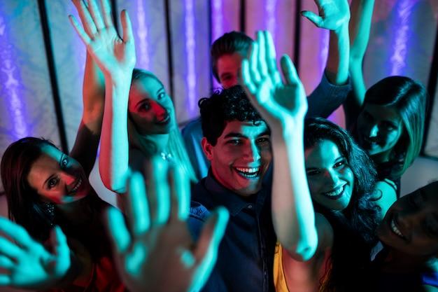 Grupo de amigos sonrientes bailando en la pista de baile