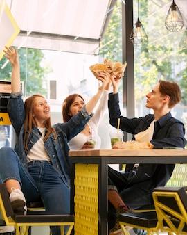 Grupo de amigos sonrientes brindando con hamburguesas