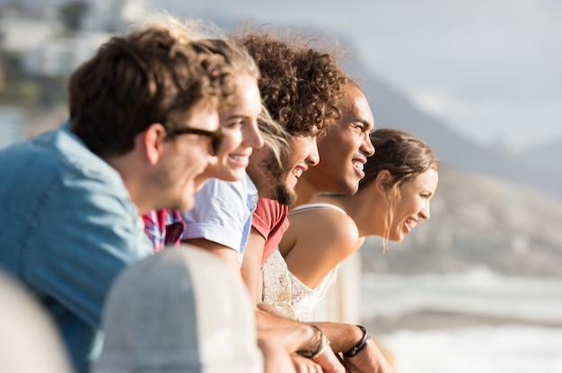Grupo de amigos sonrientes inclinado sobre la valla mientras mira al atardecer