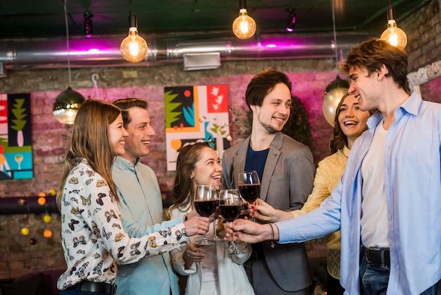 Grupo de amigos sonrientes masculinos y femeninos que tuestan el vino en club en la noche