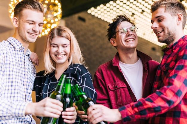 Grupo de amigos sonrientes que tuestan las botellas de cerveza en pub