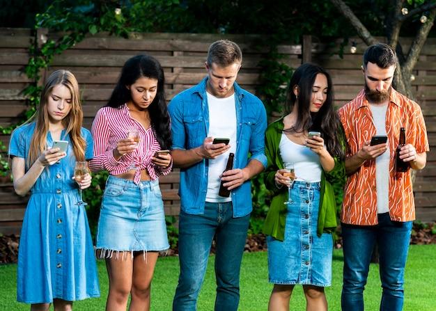 Grupo de amigos con teléfonos inteligentes al aire libre