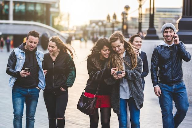 Grupo de amigos con teléfonos móviles en londres.