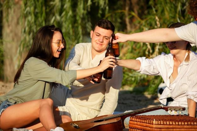 Grupo de amigos tintineando botellas de cerveza durante un picnic en la playa. estilo de vida, amistad, diversión, fin de semana y concepto de descanso.