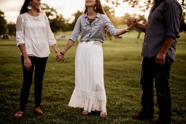 Grupo de amigos tomados de la mano en el parque y rezando
