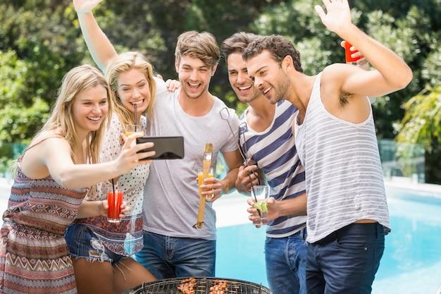 Grupo de amigos tomando una selfie cerca de la piscina