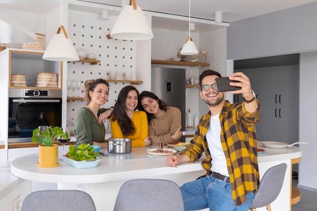 Grupo de amigos tomando un selfie en la cocina