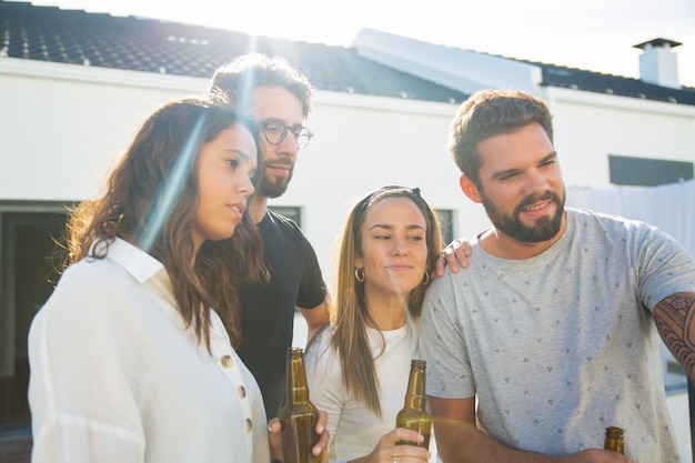 Grupo de amigos tomando selfie mientras bebe cerveza