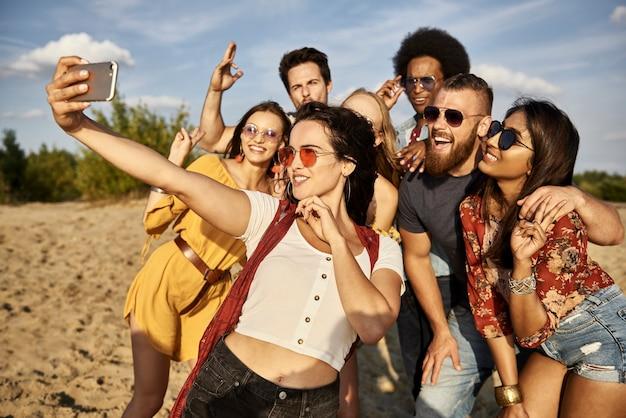Grupo de amigos tomando un selfie en la playa.
