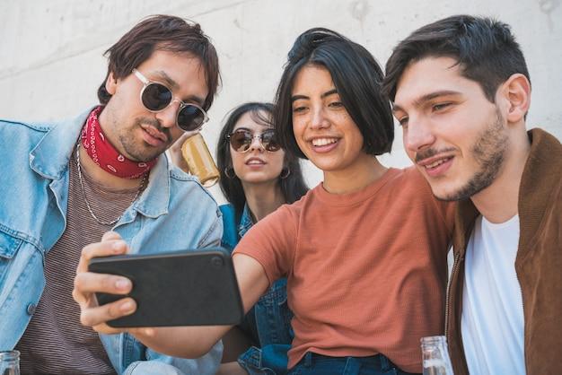 Grupo de amigos tomando una selfie con teléfono.