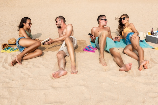 Grupo de amigos tumbados en la playa tomando un baño de sol.