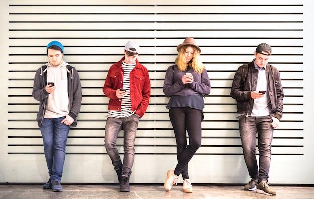 Grupo de amigos usando teléfono inteligente contra la pared en el descanso de patio de la universidad de la universidad