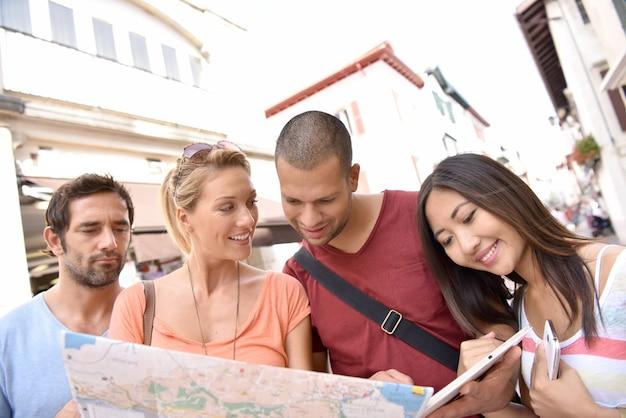 Grupo de amigos en vacaciones leyendo el mapa de la ciudad