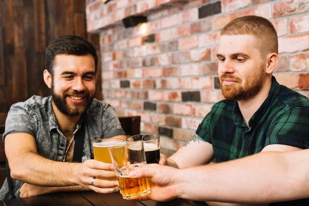 Grupo de amigos varones brindando anteojos alcohólicos en el bar