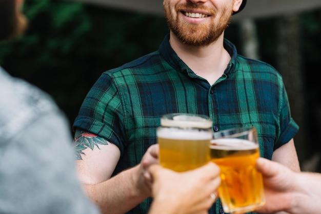 Grupo de amigos varones celebrando con un vaso de cerveza