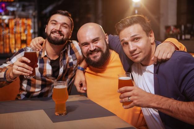 Grupo de amigos varones felices sonriendo a la cámara mientras beben cerveza juntos en el pub