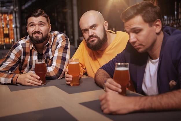 Grupo de amigos varones mirando molesto, bebiendo cerveza después de ver un partido de fútbol.