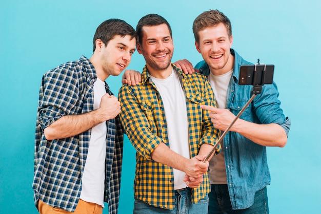 Grupo de amigos varones que toman selfie en el teléfono móvil contra el fondo azul