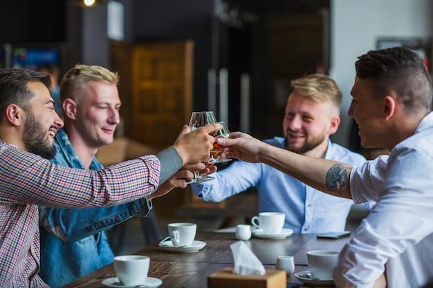 Grupo de amigos varones sentados en el restaurante brindando vasos de bebidas