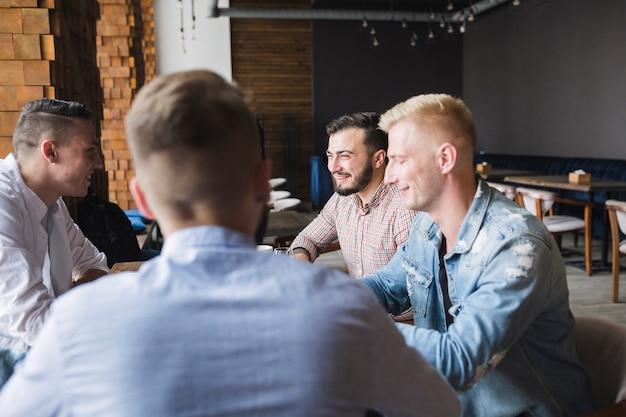 Grupo de amigos varones sentados en el restaurante
