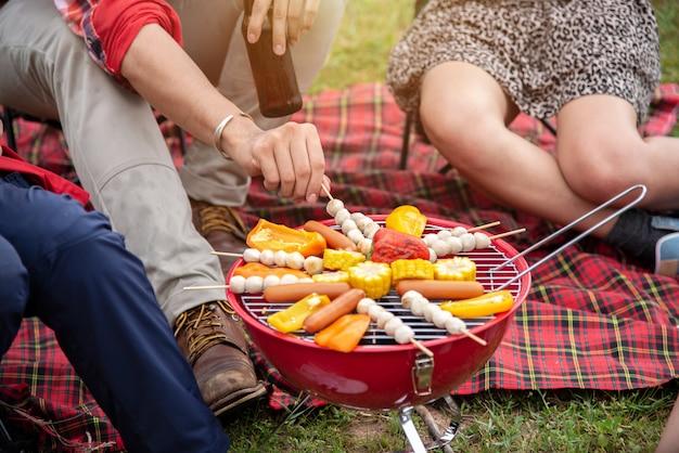 Grupo de amigos de viaje disfruta de acampar con una fiesta de barbacoa en la noche de verano