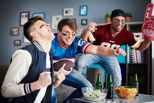 Grupo de amigos viendo fútbol en casa
