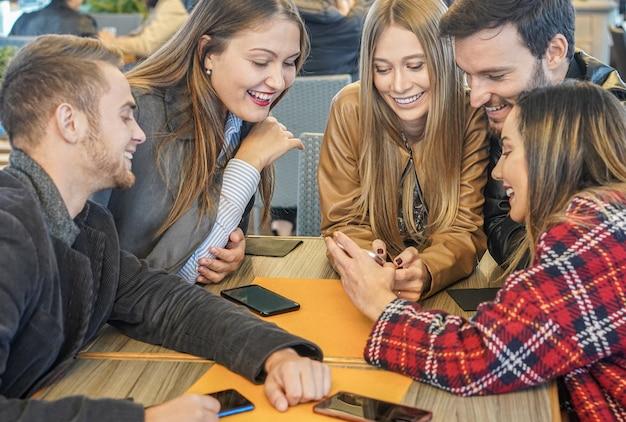 Grupo de amigos viendo teléfonos móviles y divirtiéndose