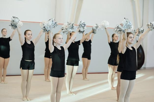Grupo de animadoras escolares positivas en ropa negra preparando baile con pompones para la competencia