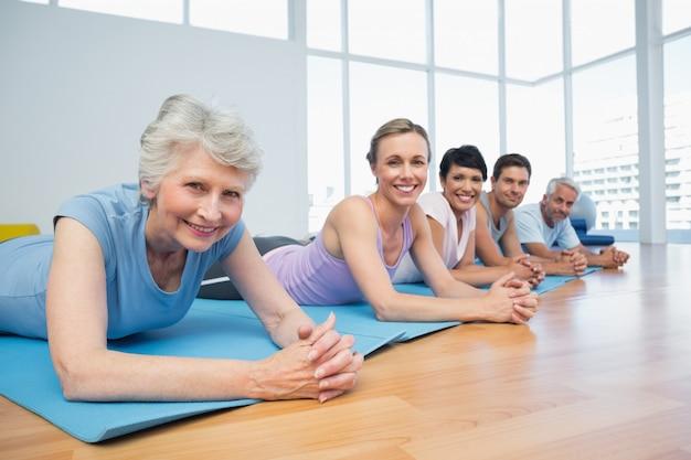 Grupo de aptitud que miente en fila en la clase de yoga