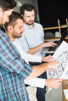 Grupo de arquitecto hombre teniendo discusión sobre blueprint