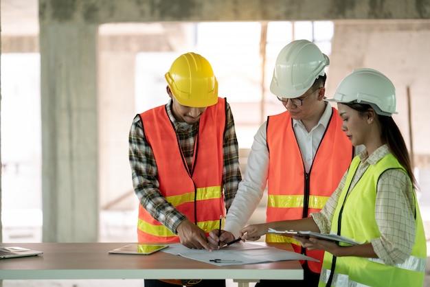 Grupo de arquitecto ingeniero y jefe de oficios reunidos sobre el plan de trabajo de construcción en el sitio de construcción