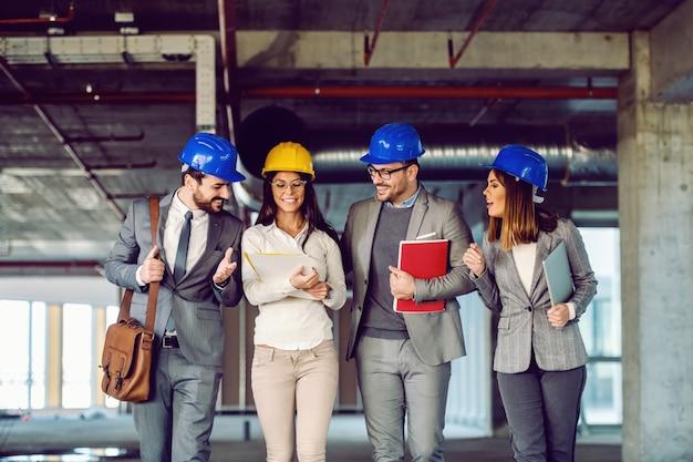 Grupo de arquitectos trabajadores dedicados exitosos que visitan el edificio en proceso de construcción.