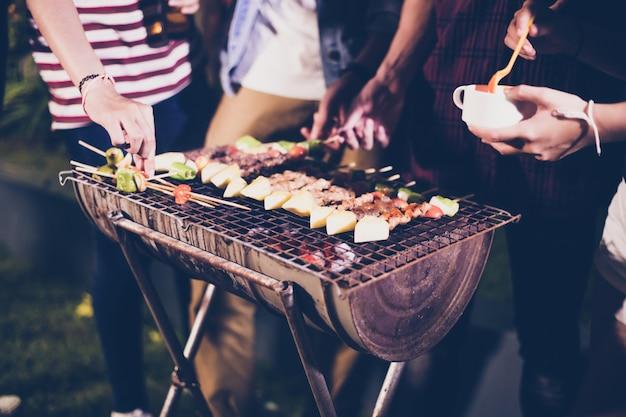Grupo asiático de amigos que tienen jardín al aire libre barbacoa riendo con bebidas alcohólicas de cerveza en la noche