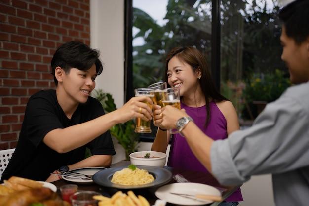 Grupo asiático joven está bebiendo cerveza y los vasos tintinean en un restaurante.