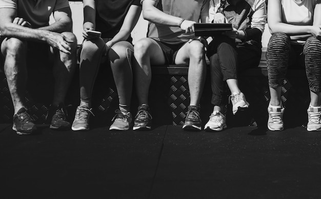 Grupo de atletas diversos sentados juntos.